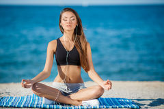 The woman meditates on a beach near the sea Royalty Free Stock Photos