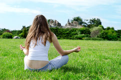 Woman meditates on green lawn Royalty Free Stock Photo