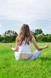 Woman meditates on green lawn on the park. Calm woman meditates on beautiful green lawn in the filds Royalty Free Stock Photo