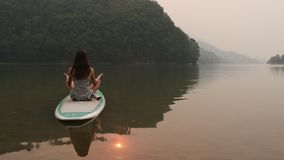 Woman meditates on paddleboard stock video footage