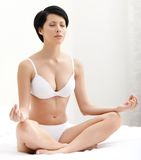 Woman meditates sitting on the bedstead Royalty Free Stock Image
