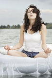 Woman meditates on the white bed in the sea Stock Photos