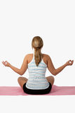 Woman meditating. Back view of a caucasian blond woman wearing exercise clothes sitting on pink mat in lotus postion meditating over white Stock Photo