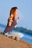 Woman meditating. On the river beach Stock Photo