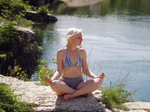 Woman meditating. On the river beach Stock Photography
