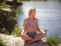 Woman meditating. On the river beach Royalty Free Stock Photos