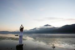 Woman Meditating. At lake by a mountain Royalty Free Stock Photography