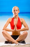 Woman meditating. Young woman doing yoga moves or meditating on beach Stock Photography
