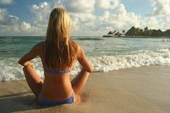 Woman meditating. On tropical ocean beach Stock Photos
