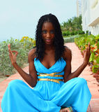 Woman Meditating. In a silky blue dress Royalty Free Stock Image