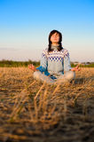Woman meditating. An attractive young woman meditating at the outdoors Stock Images