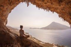 Woman meditating. Against view of Telendos Island at sunset. Kalymnos Island, Greece Stock Photo