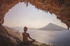 Woman meditating. Against view of Telendos Island at sunset. Kalymnos Island, Greece Royalty Free Stock Image