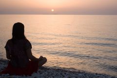 Woman meditating alone on the sea beach stock images