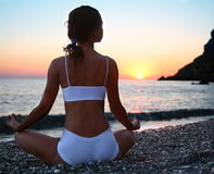 Woman meditating on the beach Stock Photography