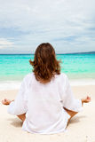 Woman meditating on beach stock photos