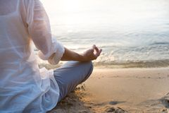 Woman meditating. On beach in lotus position Stock Photography