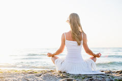 Woman meditating. On beach in lotus position Stock Photos