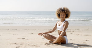 Woman Meditating On Beach In Lotus Position Stock Photos