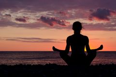 Woman meditating on the beach in lotus position. Silhouette, sun Royalty Free Stock Photo