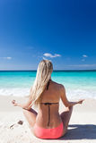 Woman meditating on beach in lotus position Royalty Free Stock Photography