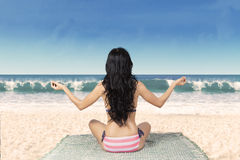 Woman meditating at beach on mat 1 Stock Photos