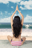 Woman meditating at beach on mat Royalty Free Stock Images