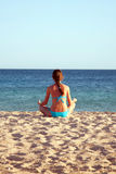 Woman meditating on beach. Rear view. Stock Image