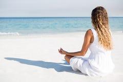 Woman meditating at beach during sunny day Stock Photo