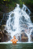 Woman meditating in beautiful waterfall Royalty Free Stock Image