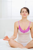 Woman meditating in bedroom Stock Photo