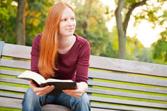 A Woman Meditating on the Bible in a Park Royalty Free Stock Photo