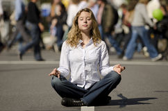 Woman meditating in busy urban street Royalty Free Stock Images