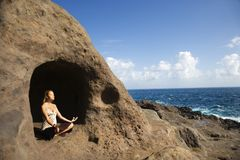 Woman meditating in cave. Royalty Free Stock Photo