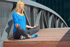 Woman  meditating  in  City Central Park in yoga lotus pose. Sport, fitness, active lifestyle , urban workout concept Royalty Free Stock Photography