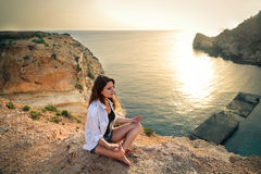 Woman meditating on a cliff stock images