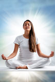 Woman meditating. Close up portrait of attractive young woman meditating with eyes closed. Front view of woman dressed in white in yoga position with ray of Royalty Free Stock Photos