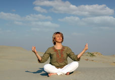 Woman meditating in desert Stock Images