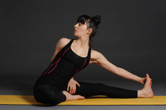 Woman meditating and doing yoga excercise against grey studio background. Stock Photography