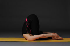 Woman meditating and doing yoga excercise against grey studio background. Royalty Free Stock Photos