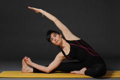 Woman meditating and doing yoga excercise against grey studio background. Stock Photo