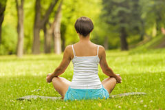 Woman meditating and doing yoga in park back. Stock Images