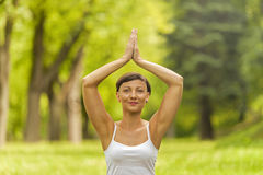Woman meditating and doing yoga in park Royalty Free Stock Image