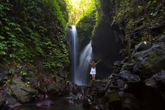 Woman meditating doing yoga between waterfalls Royalty Free Stock Photos
