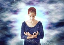Woman meditating. On a energy background Stock Photos