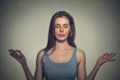 Woman meditating with eyes closed. Portrait beautiful woman meditating with eyes closed isolated on gray wall background stock photography