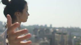 Woman meditating feeling wind on her skin, city background, female urban lover stock video
