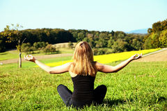 Woman meditating in the field Stock Photos
