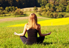 Woman meditating in the field Royalty Free Stock Image