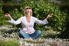 Woman meditating in garden Stock Photography
